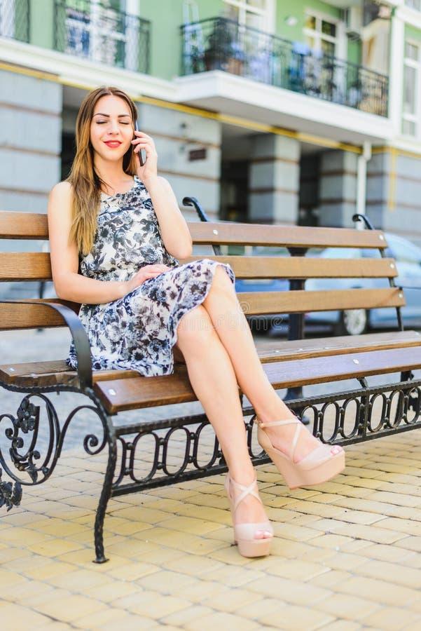 Το κορίτσι sundress κάθεται σε έναν πάγκο στοκ εικόνες