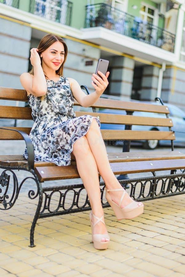 Το κορίτσι sundress κάθεται σε έναν πάγκο στοκ εικόνα με δικαίωμα ελεύθερης χρήσης