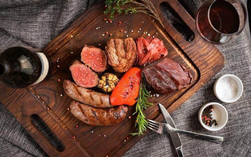 Το κρέας μιγμάτων που ψήνεται στη σχάρα στην επιτροπή με το κόκκινο κρασί στοκ φωτογραφία