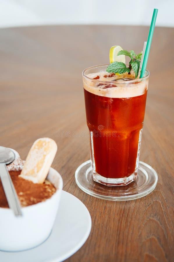 Το κρύο πάγωσε το τσάι με τη φέτα λεμονιών και τη μέντα στο ποτήρι στον ξύλινο πίνακα στοκ εικόνα