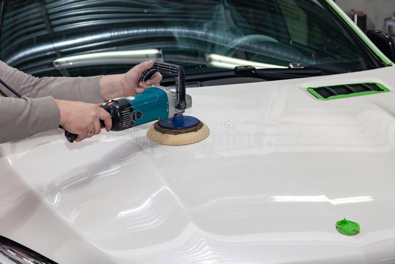 Το κύριο άτομο της απαρίθμησης στα ενδύματα εργασίας και τα βρώμικα χέρια γυαλίζει το αμάξωμα του καπό του αυτοκινήτου στο λευκό  στοκ εικόνες