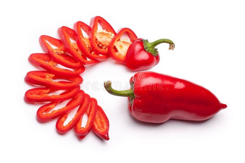 Το κόκκινο κουδουνιών πιπέρι κουδουνιών πιπεριών ολόκληρο και κόκκινο που τεμαχίστηκε στα δαχτυλίδια στο άσπρο υπόβαθρο απομόνωσε στοκ φωτογραφία με δικαίωμα ελεύθερης χρήσης