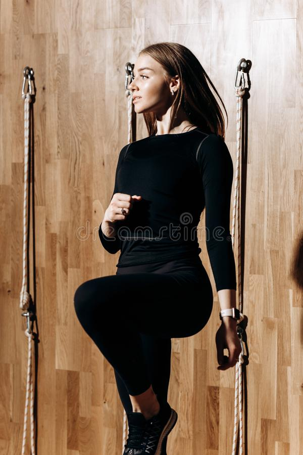 Το λεπτό κορίτσι που ντύνεται μαύρο sportswear πηδά δίπλα στον εξοπλισμό σχοινιών στη σύγχρονη γυμναστική με ξύλινο στοκ φωτογραφία