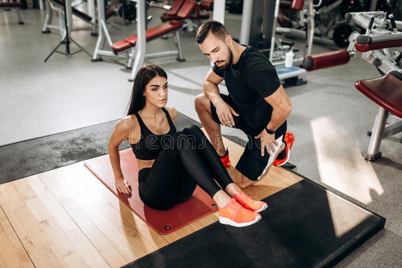 Το λεπτό κορίτσι που ντύνεται στη μαύρα αθλητικά κορυφή και τα καλσόν κάνει τις ασκήσεις για τα abdominals στο χαλί ικανότητας στ στοκ φωτογραφία