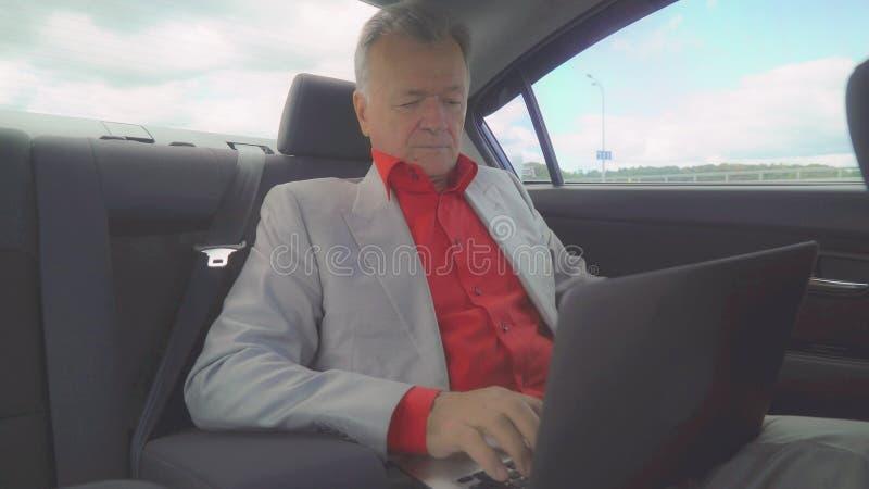 Το μέσο ηλικίας άτομο που χρησιμοποιεί το lap-top στο αυτοκίνητο κάθεται στη πίσω θέση στοκ εικόνα