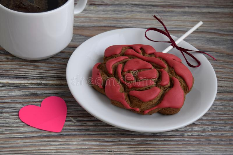 Το μελόψωμο υπό μορφή λουλουδιού ενός κοκκίνου αυξήθηκε, έγγραφο υπό μορφή καρδιάς και ένα φλυτζάνι με τον καφέ στοκ εικόνες