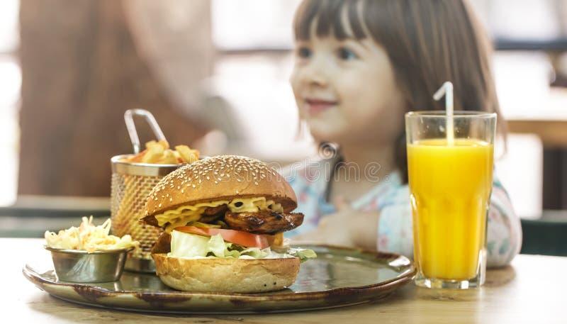 Το μικρό κορίτσι τρώει σε έναν καφέ γρήγορου φαγητού στοκ φωτογραφία με δικαίωμα ελεύθερης χρήσης