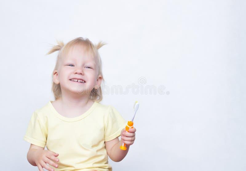 Το μικρό κορίτσι 2 χρονών με τις πλεξίδες στην τρίχα της γελά και βουρτσίζει τα δόντια της σε ένα άσπρο υπόβαθρο, διάστημα αντιγρ στοκ φωτογραφίες