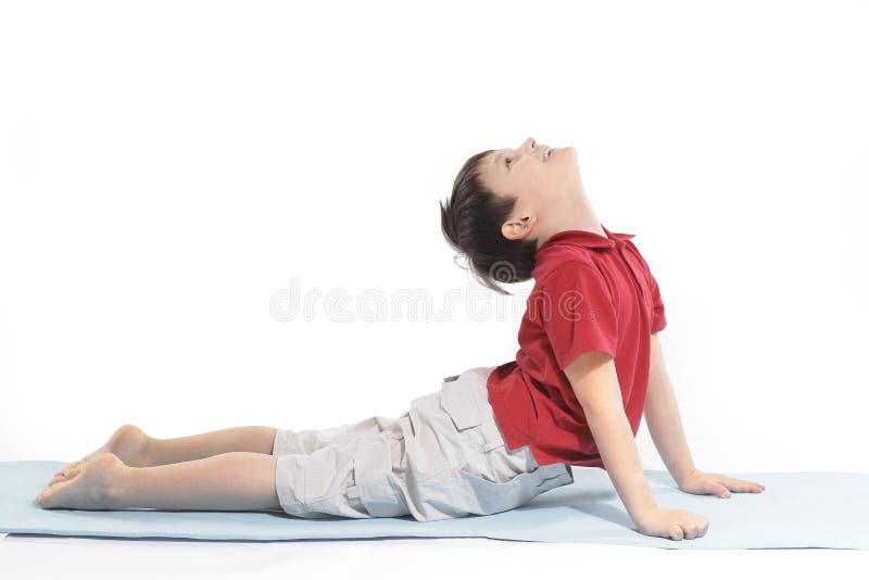 Το μικρό παιδί κάνει τις ασκήσεις πρωινού η ανασκόπηση απομόνωσε το λευκό στοκ φωτογραφία