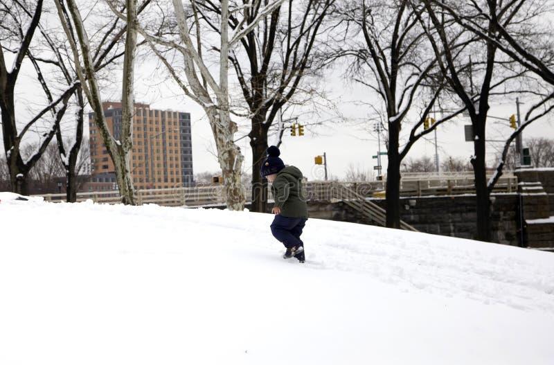 Το μικρό παιδί περπατά επάνω το λόφο χιονιού το χειμώνα στο πάρκο Bronx στοκ εικόνα με δικαίωμα ελεύθερης χρήσης