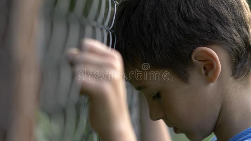 Το μόνο αγόρι έξω από το φράκτη, λυπάται για, πόνος στο πρόσωπο στοκ φωτογραφία με δικαίωμα ελεύθερης χρήσης