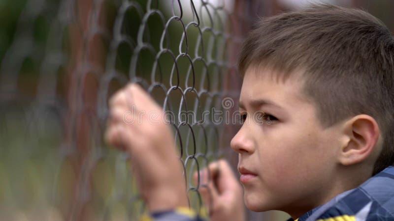 Το μόνο αγόρι χαμηλώνει το κεφάλι, λυπάται για για τη δράση, πόνος στο πρόσωπο στοκ εικόνα με δικαίωμα ελεύθερης χρήσης