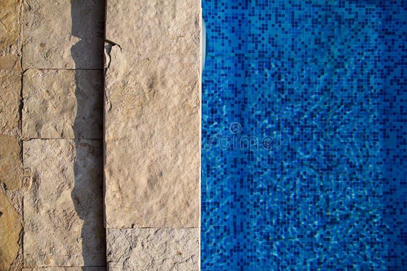 Το μπλε έσχισε το νερό στην πισίνα στο τροπικό θέρετρο με την άκρη του πεζοδρομίου Μέρος του κατώτατου υποβάθρου πισινών στοκ εικόνες με δικαίωμα ελεύθερης χρήσης