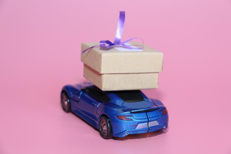 Το μπλε αθλητικό αυτοκίνητο φέρνει ένα κιβώτιο δώρων Το δώρο βρίσκεται στη στέγη του αυτοκινήτου στοκ εικόνες με δικαίωμα ελεύθερης χρήσης