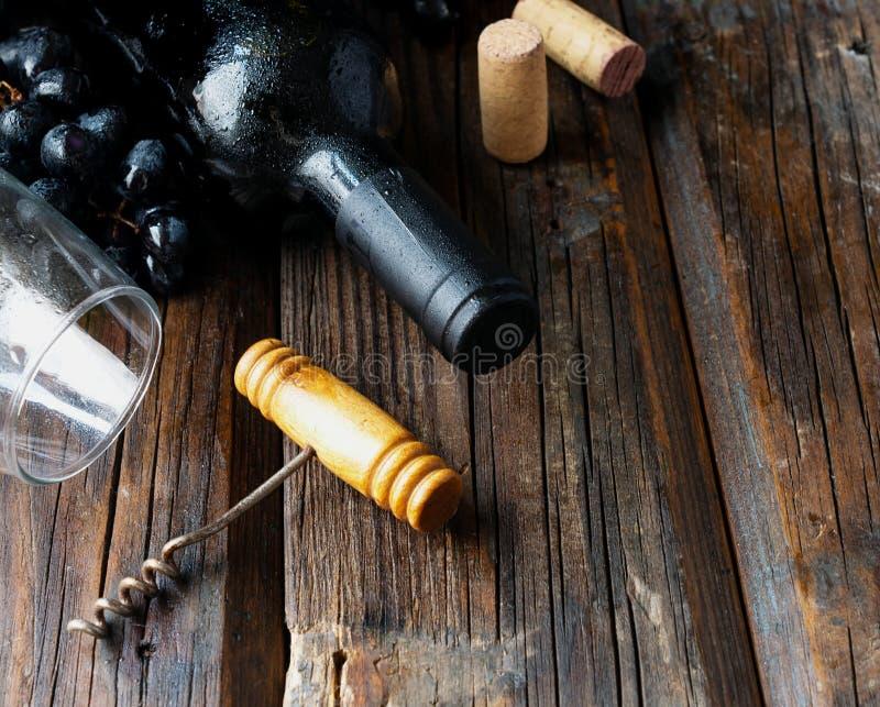 Το μπουκάλι του κόκκινου κρασιού με το φρέσκες σταφύλι και τη δέσμη βουλώνει στον ξύλινο πίνακα στοκ φωτογραφίες με δικαίωμα ελεύθερης χρήσης