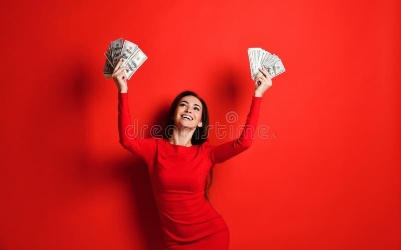 Το νέο αναιδές brunette σε ένα κόκκινο φόρεμα χαίρεται για χρήματα μεγάλου ποσού στα χέρια της που κερδίζει στοκ εικόνες