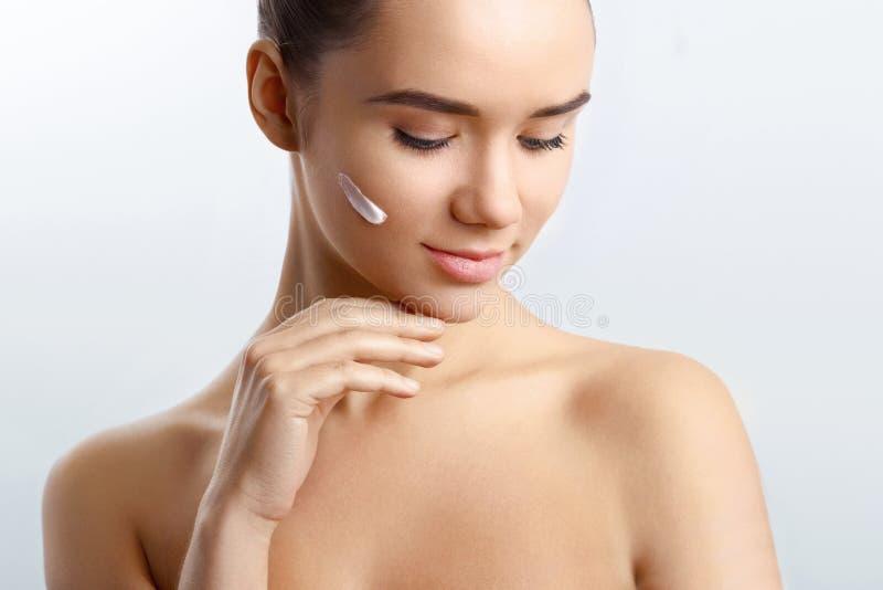 Το νέο κορίτσι καθιστά το όμορφο πρόσωπό της φρέσκο και σαφές με τη βοήθεια της κρέμας Δέρμα που εφαρμόζει το ενυδατικό λοσιόν στοκ εικόνες με δικαίωμα ελεύθερης χρήσης