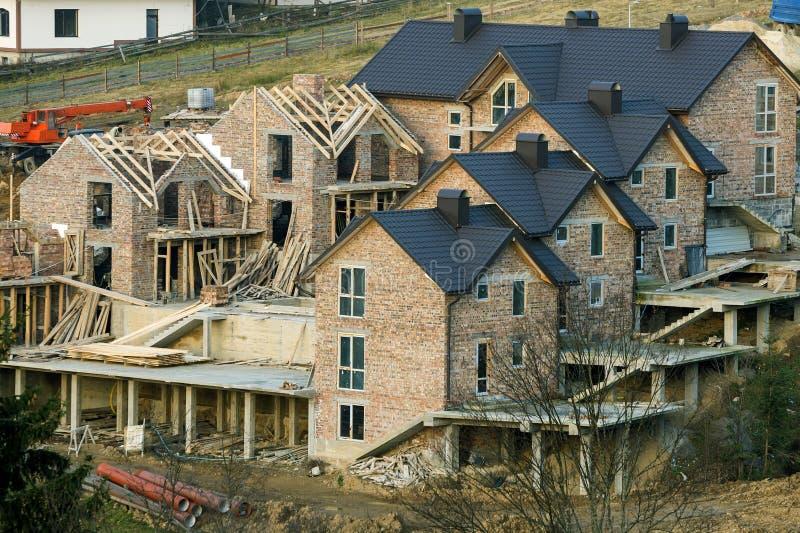 Το νέο μεγάλο ευρύχωρο ατελές σπίτι τούβλου, συγκυριαρχία μεγάρων με καφετή η στέγη κάτω από την κατασκευή Αρχιτεκτονική λύση, στοκ φωτογραφία