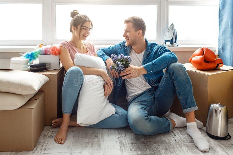 Το νέο οικογενειακό ζεύγος αγόρασε ή νοικίασε το πρώτο μικρό διαμέρισμά τους Οι καλοί εύθυμοι άνθρωποι κάθονται μαζί στο πάτωμα μ στοκ εικόνες
