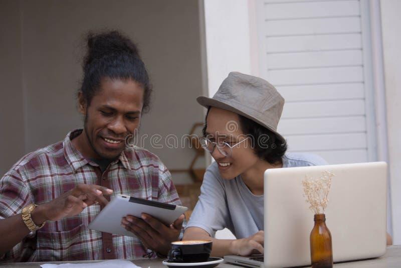 Το νέο δημιουργικό άτομο δύο συζητά με το lap-top και την ταμπλέτα, νέους Ασιάτη και το μαύρο που λειτουργούν με την ταμπλέτα και στοκ εικόνες