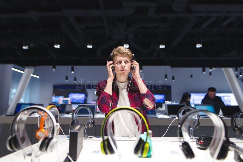 Το νέο, όμορφο άτομο ακούει τη μουσική σε ένα σύγχρονο κατάστημα τεχνολογίας Επιλέξτε και αγοράστε τα ακουστικά στο κατάστημα στοκ φωτογραφίες