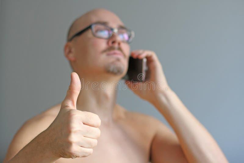 Το νέο όμορφο άτομο στα μαύρα γυαλιά μιλά στο τηλέφωνο απομονωμένο κινηματογράφ&e Ένα άτομο παρουσιάζει αντίχειρα Όλα είναι μεγάλ στοκ εικόνα