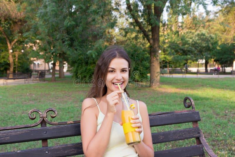 Το νέο όμορφο κορίτσι πίνει τη λεμονάδα από το μπουκάλι μέσω του αχύρου με μια μεγάλη ευχαρίστηση στοκ εικόνες