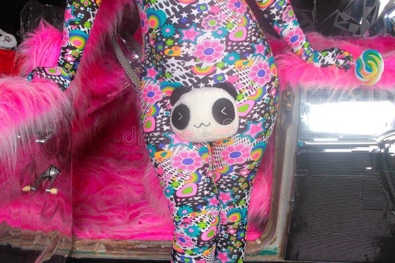 Το ξανθό κορίτσι κομμάτων λεσχών στο οξύ anime ορίζει spandex catsuit με το αυτοκίνητο καθρεφτών με τη ρόδινη γούνα έτοιμη για τη στοκ εικόνα