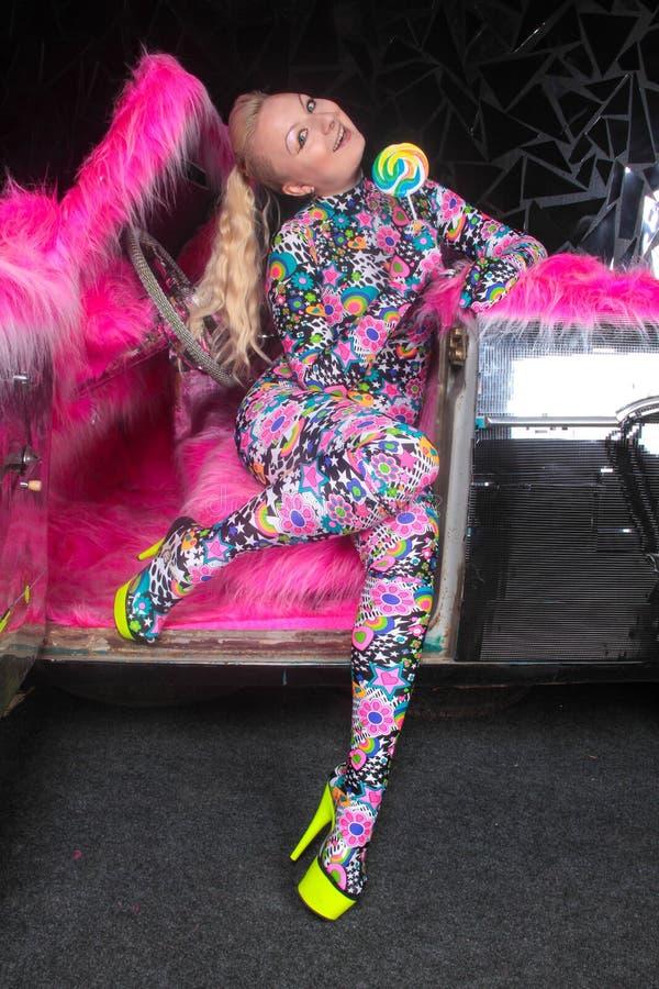 Το ξανθό κορίτσι κομμάτων λεσχών στο οξύ anime ορίζει spandex catsuit με το αυτοκίνητο καθρεφτών με τη ρόδινη γούνα έτοιμη για τη στοκ φωτογραφίες με δικαίωμα ελεύθερης χρήσης