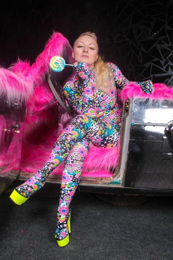 Το ξανθό κορίτσι κομμάτων λεσχών στο οξύ anime ορίζει spandex catsuit με το αυτοκίνητο καθρεφτών με τη ρόδινη γούνα έτοιμη για τη στοκ φωτογραφίες
