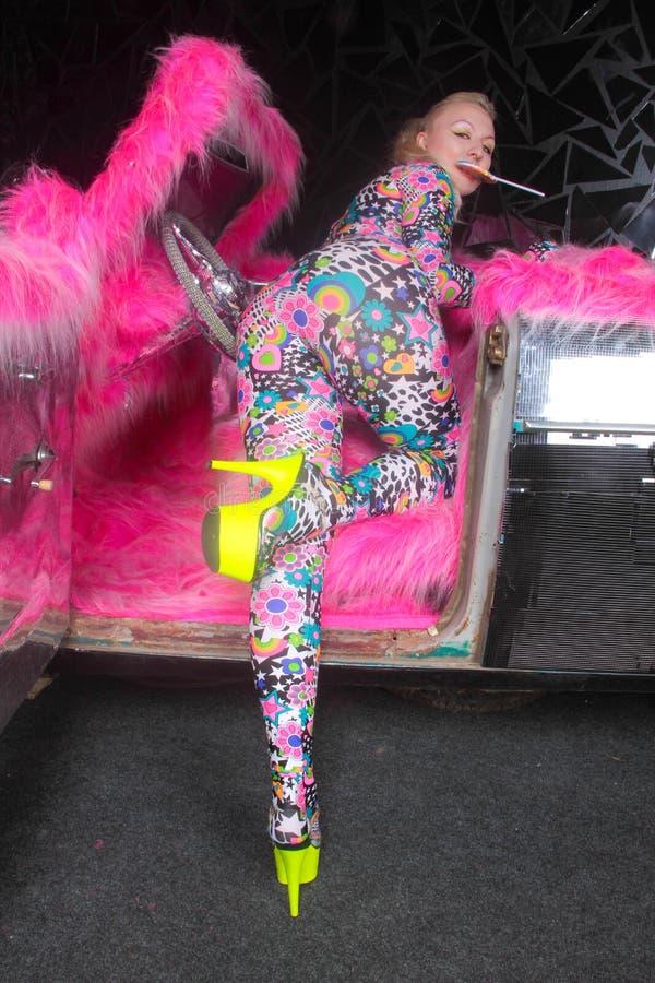 Το ξανθό κορίτσι κομμάτων λεσχών στο οξύ anime ορίζει spandex catsuit με το αυτοκίνητο καθρεφτών με τη ρόδινη γούνα έτοιμη για τη στοκ φωτογραφία