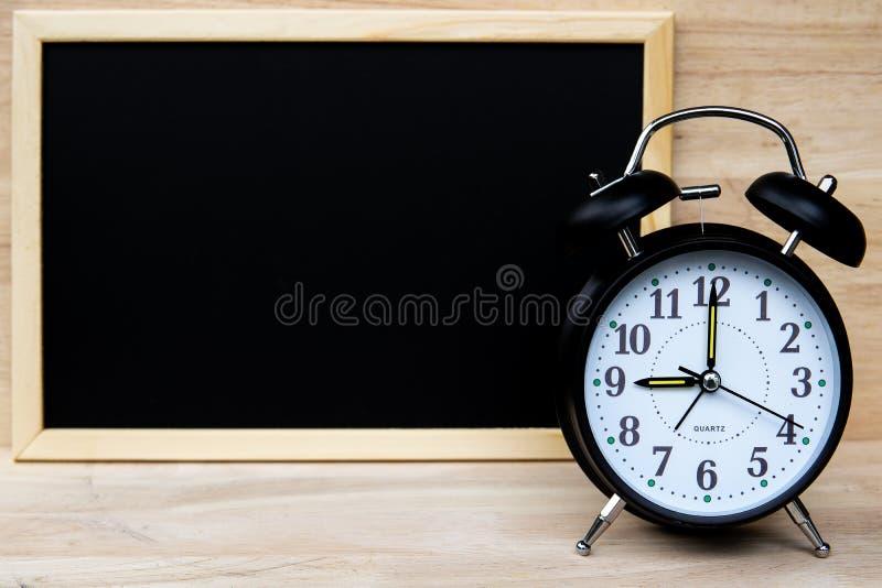 Το ξυπνητήρι και ο πίνακας κιμωλίας ή ο πίνακας για το κείμενό σας παρουσιάζουν σχέδιο πινάκων με το χρόνο και πίσω στη σχολική έ στοκ εικόνες