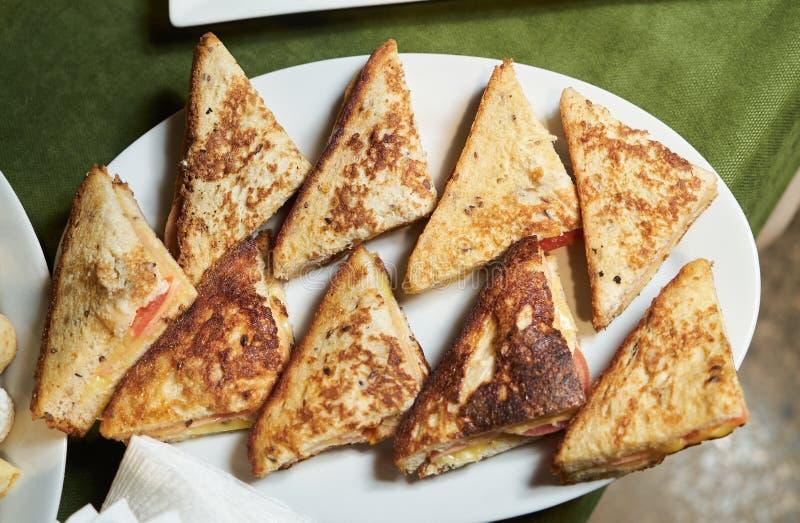 Το διάφορο τρίγωνο ψήνει τα σάντουιτς σε ένα άσπρο πιάτο, κινηματογράφηση σε πρώτο πλάνο στοκ εικόνες με δικαίωμα ελεύθερης χρήσης