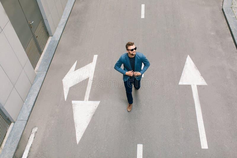 Το όμορφο άτομο στα γυαλιά ηλίου περπατά στην οδό Φορά το γκρίζο σακάκι, τζιν, καφετιά παπούτσια, γενειάδα επάνω από την όψη στοκ εικόνες με δικαίωμα ελεύθερης χρήσης