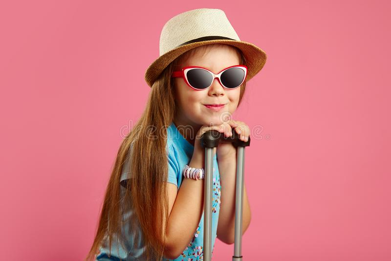 Το όμορφο κορίτσι επτά ετών στα γυαλιά ηλίου και το καπέλο αχύρου, κλίνει στη λαβή της βαλίτσας, στέκεται στο απομονωμένο ροζ στοκ φωτογραφία