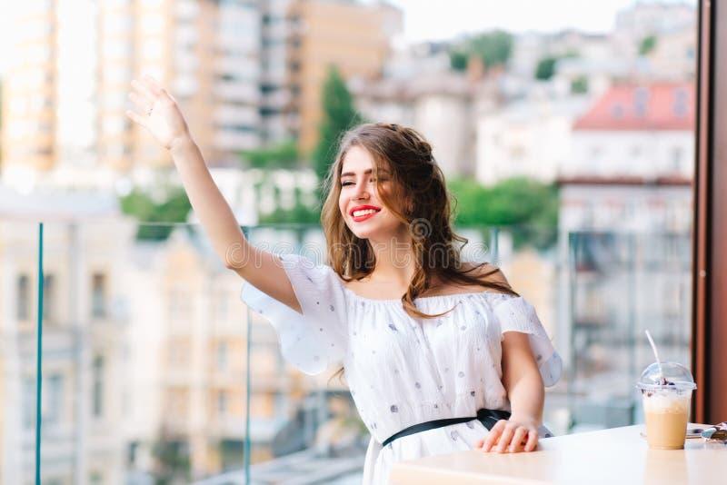 Το όμορφο κορίτσι με μακρυμάλλη στον πίνακα στο πεζούλι στον καφέ Φορά ένα άσπρο φόρεμα με το γυμνό ώμο στοκ φωτογραφίες