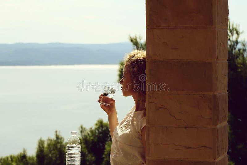 Το όμορφο κορίτσι πίνει το νερό στοκ φωτογραφία