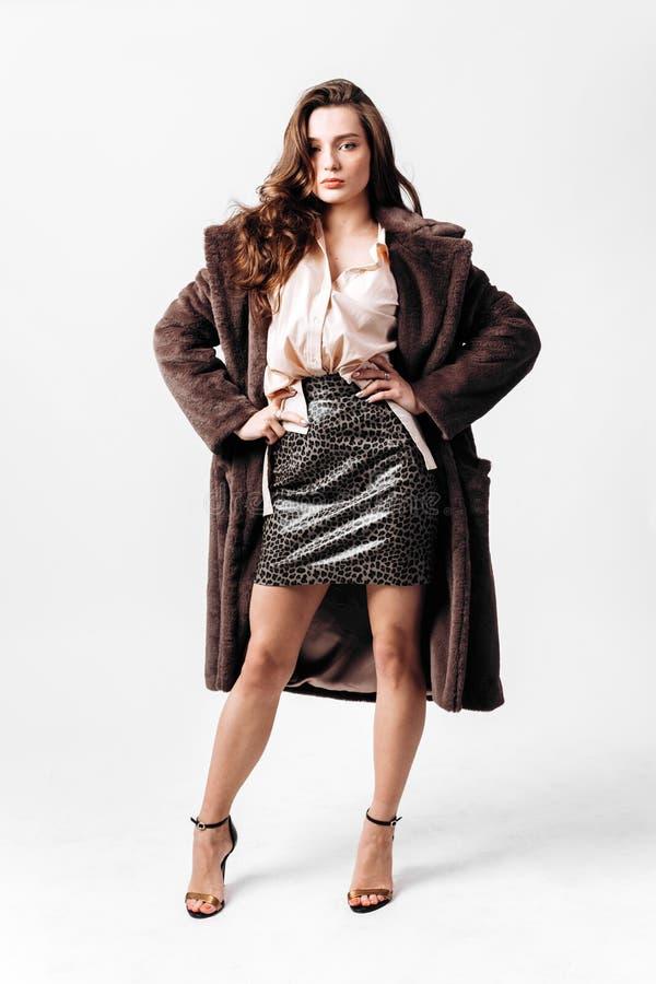 Το όμορφο κορίτσι που ντύνεται σε ένα πουκάμισο, μια φούστα λεοπαρδάλεων και ένα παλτό γουνών στα υψηλά τακούνια θέτει στο άσπρο  στοκ φωτογραφία με δικαίωμα ελεύθερης χρήσης