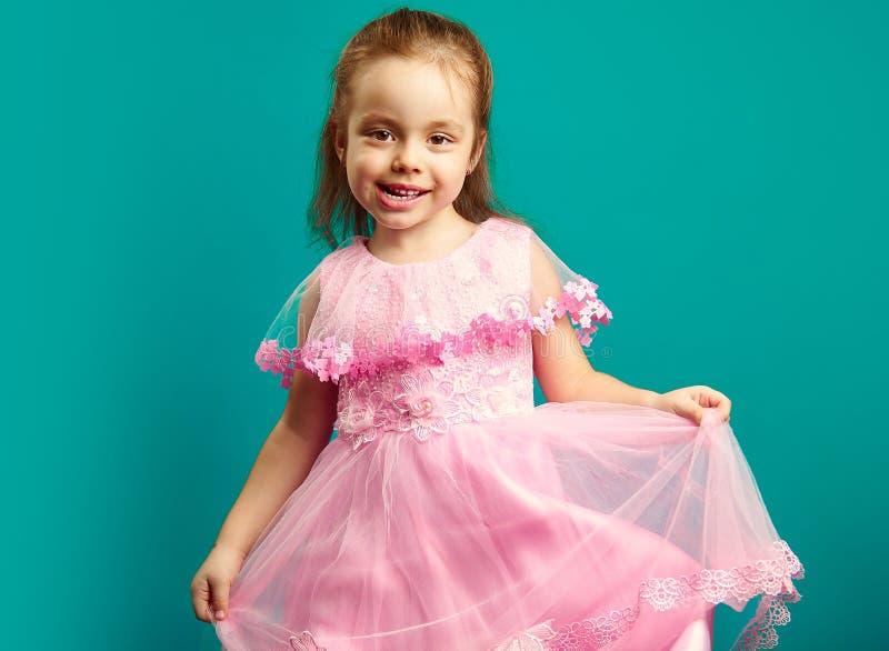Το όμορφο κοριτσάκι φορά το ρόδινο φόρεμα στο μπλε στοκ εικόνα με δικαίωμα ελεύθερης χρήσης