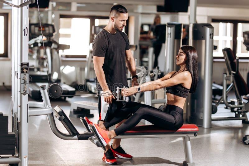 Το όμορφο λεπτό κορίτσι που ντύνεται στα μαύρα αθλητικά ενδύματα κάνει τις ασκήσεις για τα abdominals σε μια ειδική μηχανή άσκηση στοκ φωτογραφία με δικαίωμα ελεύθερης χρήσης