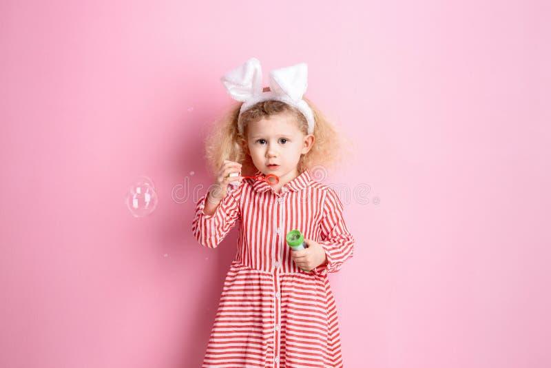 Το όμορφο μικρό κορίτσι στα αυτιά ριγωτών κόκκινων και άσπρων φορεμάτων και λαγουδάκι στο κεφάλι της διογκώνει τις φυσαλίδες σαπο στοκ φωτογραφία