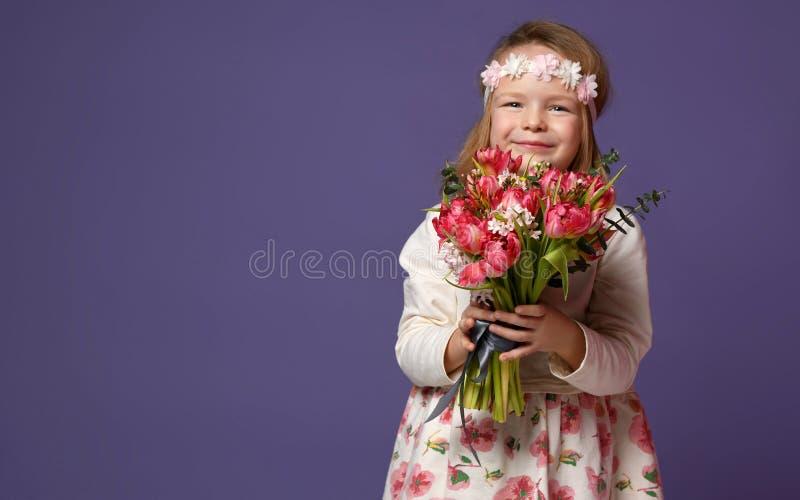 Το όμορφο μικρό κορίτσι στο στεφάνι των άσπρων λουλουδιών με την ανθοδέσμη των τουλιπών άνοιξη ανθίζει για το ευτυχές χαμόγελο στ στοκ εικόνα