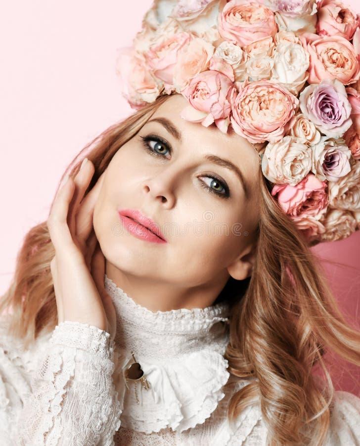 Το όμορφο νέο πορτρέτο γυναικών μόδας με τα λεπτά τριαντάφυλλα ανθίζει στην τρίχα με το στεφάνι λουλουδιών στο ροζ στοκ φωτογραφία