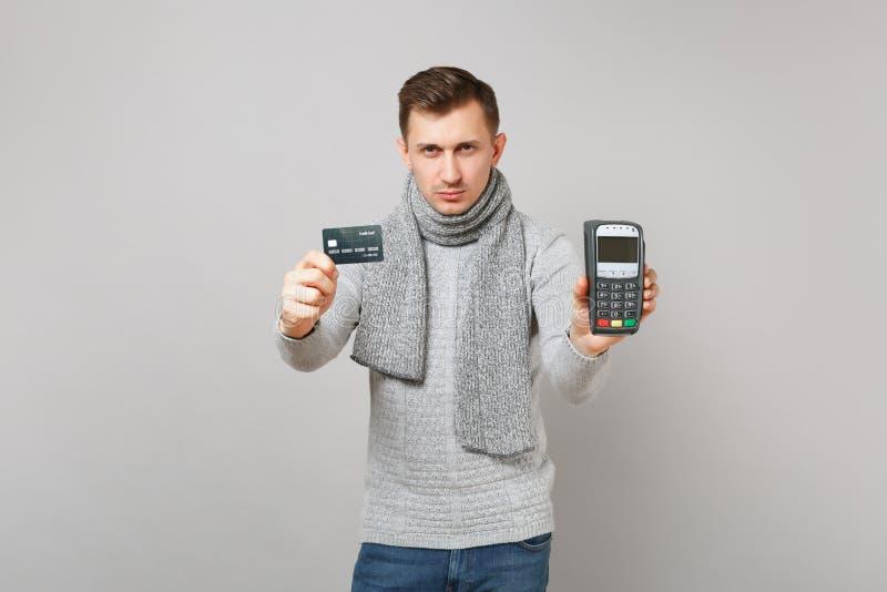 Το σοβαρό άτομο που κρατά το ασύρματο σύγχρονο τερματικό πληρωμής τραπεζών στη διαδικασία, αποκτά τις πληρωμές με πιστωτική κάρτα στοκ φωτογραφία