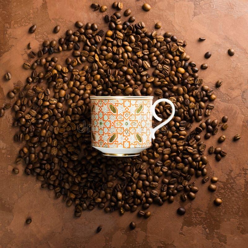 Το φλυτζάνι για τον καφέ βρίσκεται στα διεσπαρμένα φασόλια καφέ σε ένα σκοτεινό καφετί κατασκευασμένο υπόβαθρο φρέσκια ελιά πετρε στοκ εικόνες