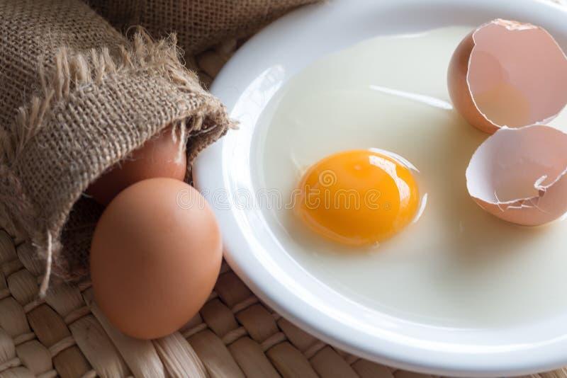 Το φρέσκο σπασμένο αυγό με το λέκιθο στο άσπρο πιάτο, ακατέργαστα αυγά με sackcloth αυγών στην καφετιά τσάντα, φωτογράφισε στο ξύ στοκ εικόνα με δικαίωμα ελεύθερης χρήσης