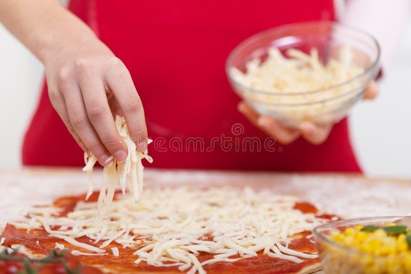 Το χέρι ψεκάζει το ξυμένο τυρί στην πίτσα στοκ φωτογραφία με δικαίωμα ελεύθερης χρήσης