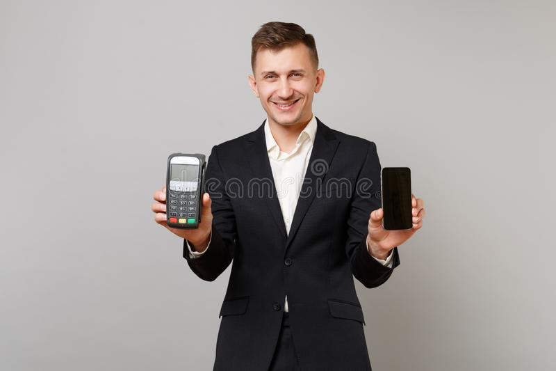 Το χαμογελώντας επιχειρησιακό άτομο που κρατά το ασύρματο σύγχρονο τερματικό πληρωμής τραπεζών στη διαδικασία, αποκτά τις πληρωμέ στοκ εικόνα