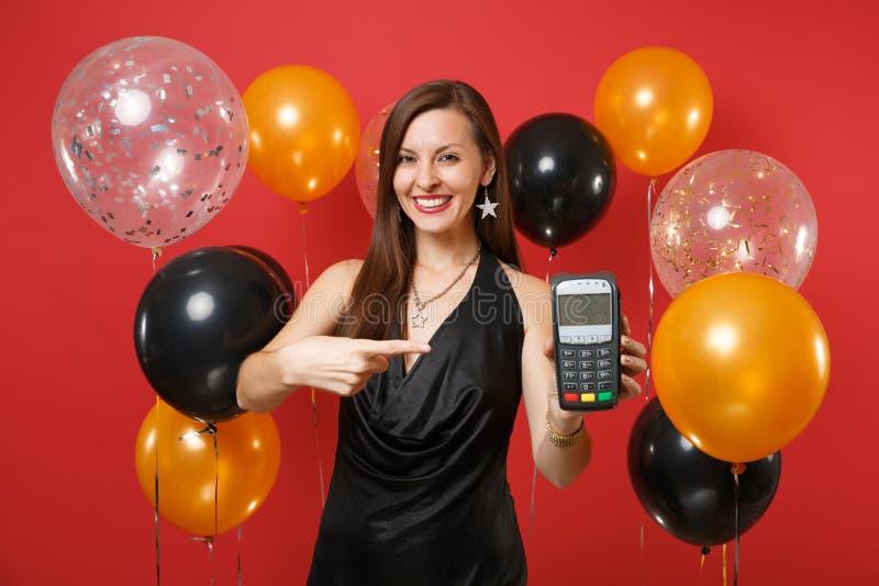 Το χαμογελώντας κορίτσι στο μαύρο φόρεμα που κρατά το ασύρματο σύγχρονο τερματικό πληρωμής τραπεζών στη διαδικασία, αποκτά τις πλ στοκ εικόνα