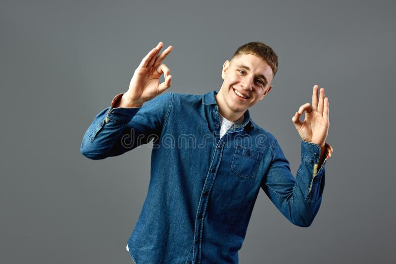 Το χαμόγελο του τύπου που ντύνεται σε ένα πουκάμισο τζιν παρουσιάζει με τα δάχτυλά του εντάξει σημάδια στο στούντιο στο γκρίζο υπ στοκ φωτογραφία